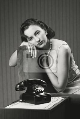 Kobieta ubrana lingeriee czeka na telefon, aby zadzwonić