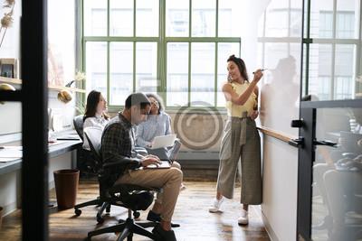 Naklejka Kobieta używa whiteboard w małym drużynowym spotkaniu
