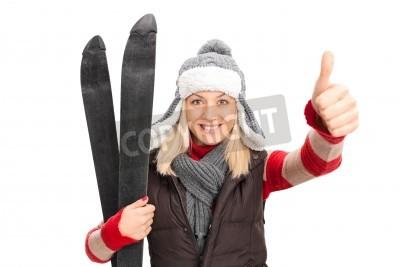 Naklejka Kobieta w zimowe ubrania gospodarstwa Narty i podając kciuk w górę na białym tle