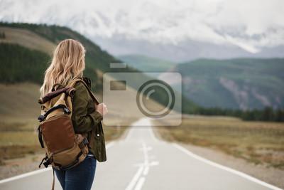 Naklejka Kobieta z plecakiem i drogą rozciągającą się w dal na tle gór