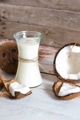 Naklejka Kokos z olejem kokosowym w słoju na drewnianym tle