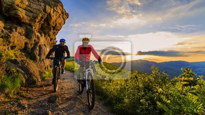 Naklejka Kolarstwo górskie kobiet i mężczyzna jedzie na rowerach w górach słońca krajobraz lasów. Para jeździła na torze MTB enduro. Aktywność sportowa na świeżym powietrzu.