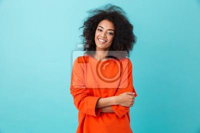 Naklejka Kolorowy portret zadziwiająca kobieta w czerwonej koszula z afro fryzurą patrzeje na kamerze z uśmiechem, odizolowywający nad błękitnym tłem