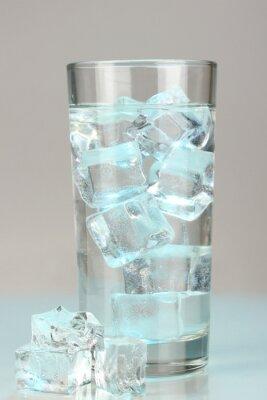 Naklejka Kostki lodu w szklance na jasnoniebieskim tle