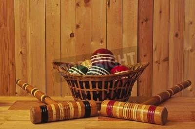 koszyk piłek do krokieta oraz pałkami na tle drewna