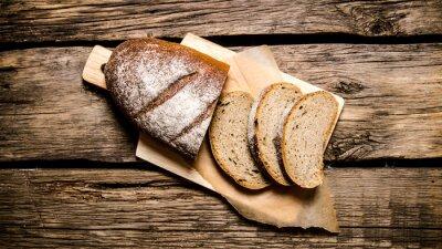 Naklejka Krojonego chleba żytniego na desce. Na drewnianym stole.