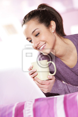 ładna dziewczyna uśmiecha się do laptopa z filiżanką kawy w ręku