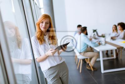 Naklejka Ładna młoda czerwona włosiana kobieta używa cyfrową pastylkę