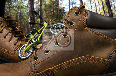 Naklejka Leather travelling boots in woods.