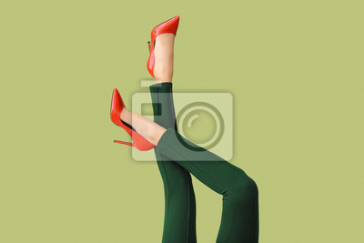 Naklejka Legs of young woman in high-heeled shoes and pants on color background