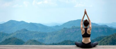 Naklejka Lifestyle woman yoga exercise and pose for healthy life. Young girl or people pose balance body vital zen and meditation for workout nature mountain background in morning day. Copy space for banner.