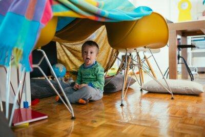 Naklejka little boy playing in his built indoor fort in living room