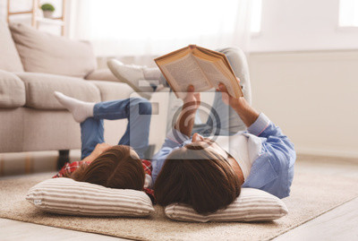 Naklejka Little girl and father enjoying book together, laying on floor