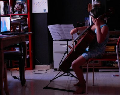 Naklejka little girl teaching cello from home with computer via video conference