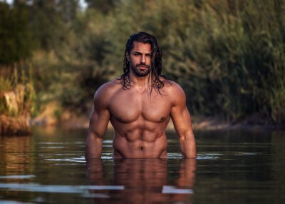 Naklejka Long haired bearded muscular man shirtless stands waist deep in the water. Aquaman in the water. Tanned attractive guy with long dark wet hair