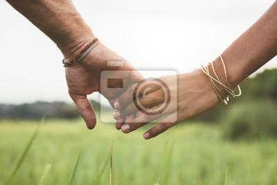 Naklejka Loving para trzymając się za ręce w polu