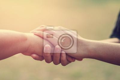 Naklejka ludzie starzy i młodzi ręki mienia z zmierzchu tłem