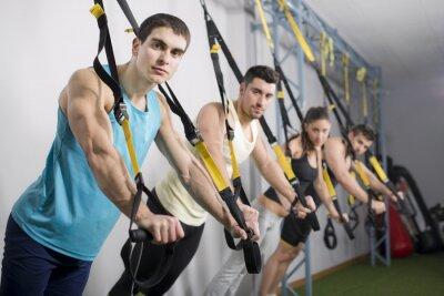 Naklejka Ludzie w siłowni robi ćwiczenia linowe trx