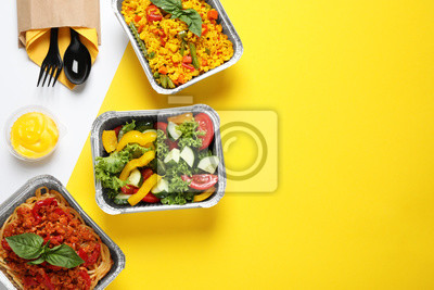 Naklejka Lunchboxes on color table, flat lay. Healthy food delivery