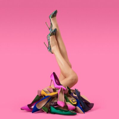 Naklejka Luxurious beautiful female legs in high-heeled boat shoes, around a lot of multi-colored shoes made of leather and fabric, on a pink background, shoe advertising, banner, mock-up