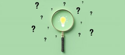 Naklejka magnifying glass with lightbulb as symbol for finding a solution on light green background