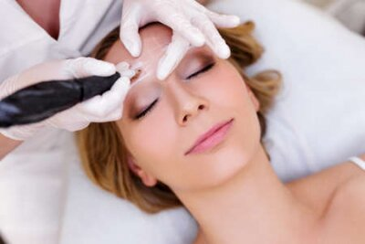 Naklejka make up and beauty concept - close up of beautician applying permanent make up on eyebrows