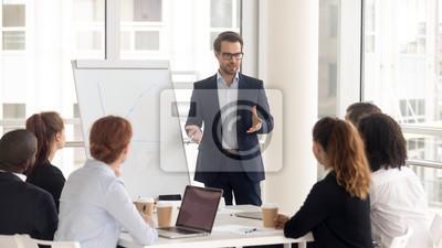 Naklejka Male business coach speaker in suit give flipchart presentation