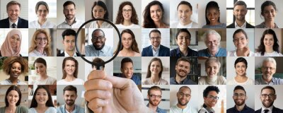 Naklejka Male employer holding magnifier in hand finding unique talent african ethnic job candidate choosing among many lot of multiethnic people different faces collage. Recruiting, human resources concept.