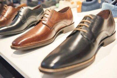 Naklejka male footwear selling. Formal leather shoes at shelf in shop window
