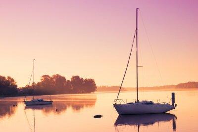 Naklejka Małe łodzie żaglowe odzwierciedlenia w spokojnej wodzie podczas wschodu słońca.
