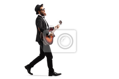 Naklejka Male musician walking and playing an acoustic guitar