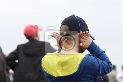 Mały chłopiec zamyka uszy od hałasu