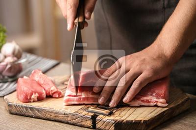 Naklejka Man cutting fresh raw meat on table in kitchen, closeup