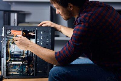 Naklejka man disassembling and reassembling the computer, close up side view photo.