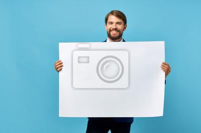 Naklejka man holding a white blank on a blue background