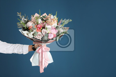 Naklejka Man holding beautiful flower bouquet on blue background, closeup view. Space for text