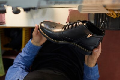 Naklejka Man holding black leather boot. Close up shot from above of new stylish footwear in hands of shoe factory worker. Concept of shoe manufacturing industry. Top view, closeup