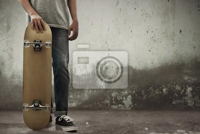 Naklejka Man holding skateboard on the street