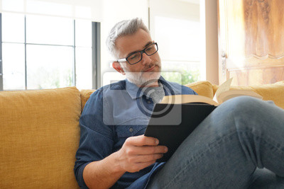 Naklejka Man in 40s reading book in modern home