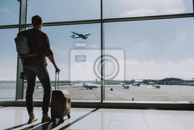 Naklejka Man is watching plane flying from airport