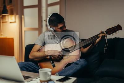Naklejka man playing guitar at his home