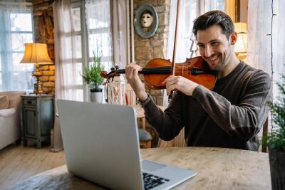Naklejka Man student learns to play the violin online using a laptop.