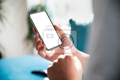 Naklejka Man using smartphone blank screen frameless modern design while lying on the sofa in home interior