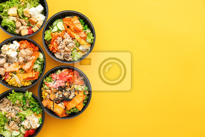 Naklejka Many containers with delicious food on color background