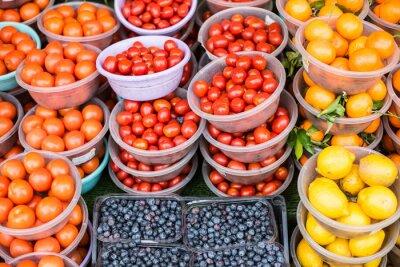 Naklejka Market Display Of Fresh Fruits Including Lemons, Oranges, Blueberries, And Tomatoes