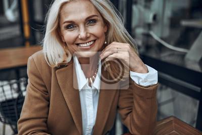 Naklejka Mature woman outdoors expressing happiness stock photo