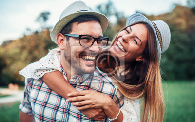 Naklejka Meeting in the park. Boyfriend carrying his girlfriend on piggyback. Love, dating, romance