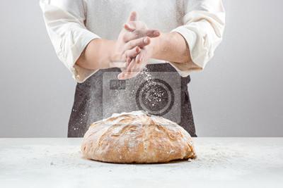 Naklejka Męskie dłonie w mące i tamtejsze bochenek chleba ekologicznej