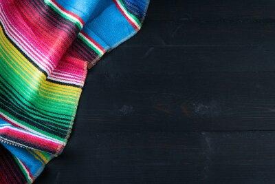 Naklejka Mexican poncho on black background. Copy space.