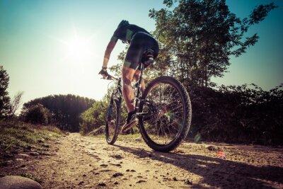 Naklejka Mężczyzna jedzie na brudnej drodze na rowerze górskim